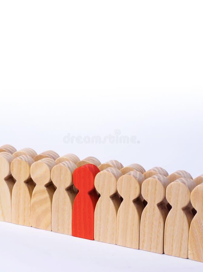 De gekozen persoon onder andere Een menselijk cijfer van rode kleur bevindt zich in de menigte Houten cijfers van mensen Een bega royalty-vrije stock foto's
