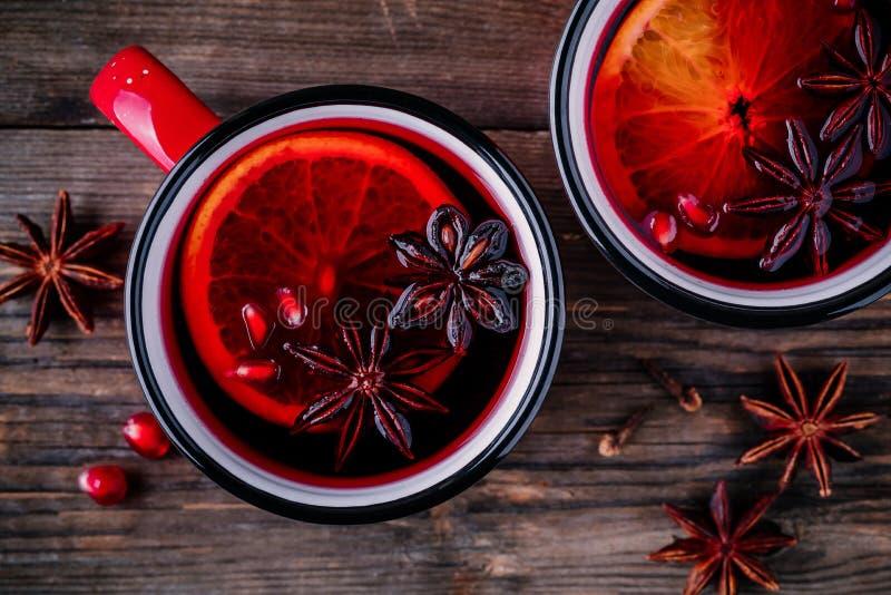 De gekruide Cider van Granaatappelapple overwoog Wijnsangria in rode mokken op houten achtergrond royalty-vrije stock foto's