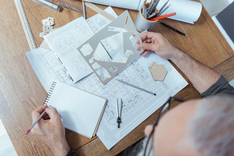 De gekwalificeerde bejaarde architect werkt op zijn project stock foto