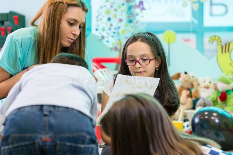 De gekwalificeerde coördinerende kinderen van de kleuterschool vrouwelijke leraar royalty-vrije stock foto's