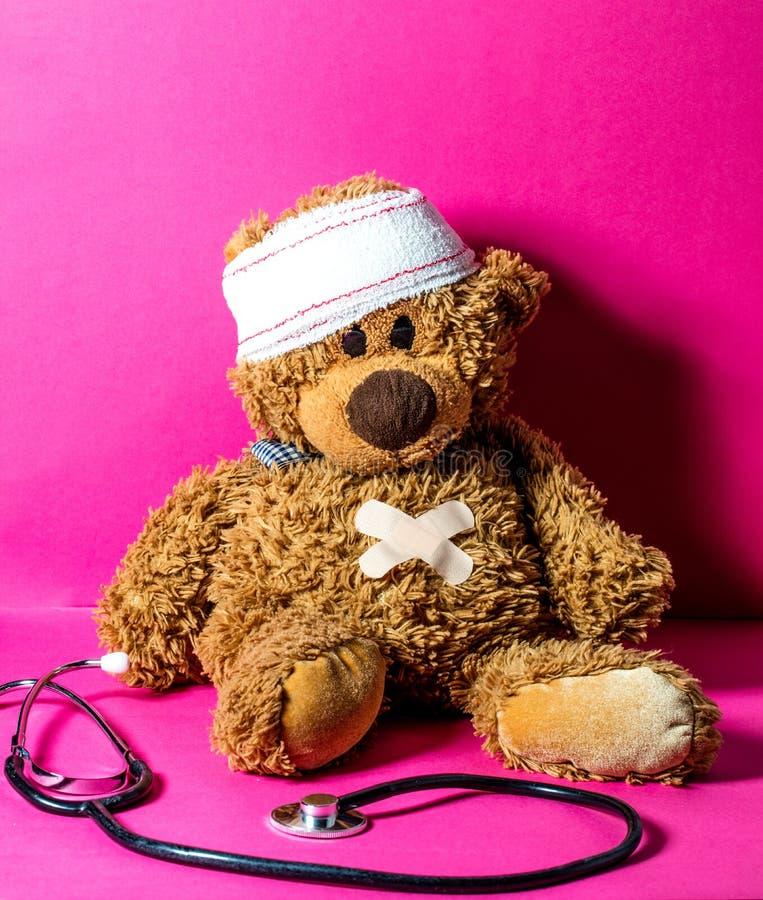 De gekwetste teddybeer van het kind met maag en hoofdverband stock afbeelding