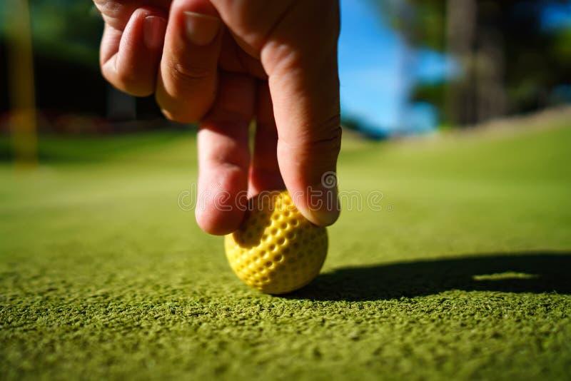 De gele bal van Mini Golf op groen gras bij zonsondergang stock afbeelding