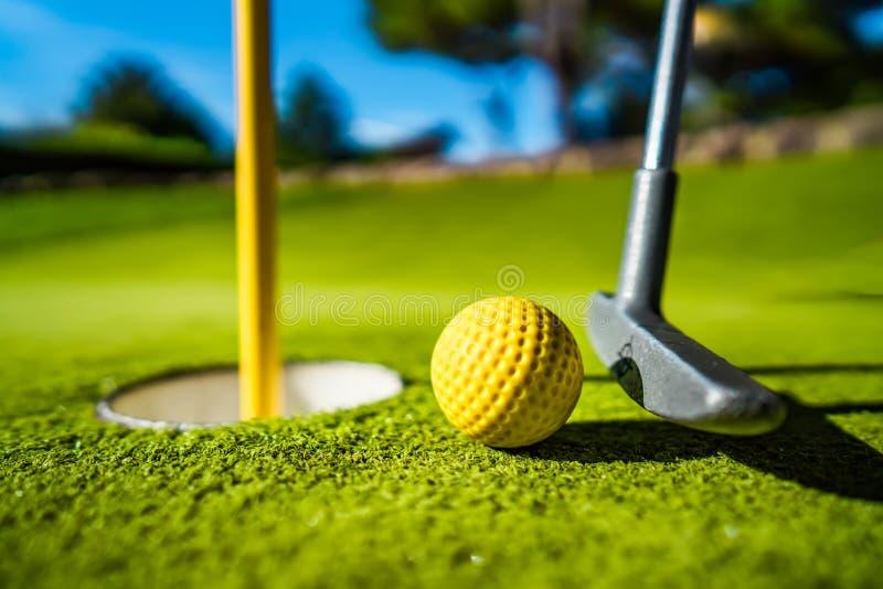 De gele bal van Mini Golf op groen gras bij zonsondergang stock foto