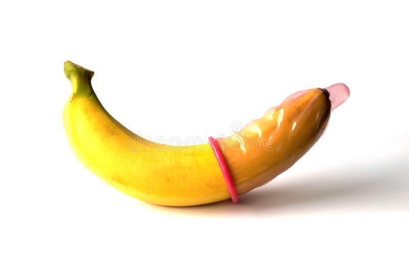 De gele banaankromme die een condoom dragen isoleert op witte achtergrond stock afbeelding
