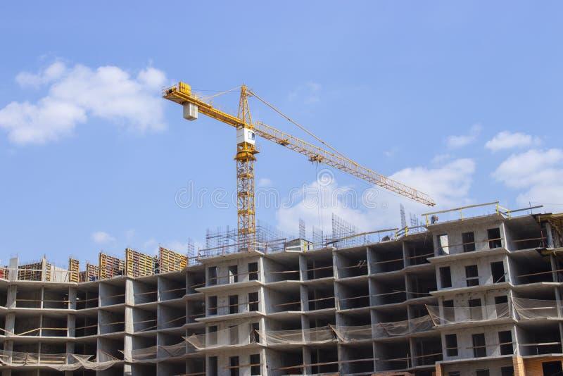De gele bouwkraan werkt aan de bouw van woningbouw met meerdere verdiepingen De apparatuur van de bouw stock fotografie