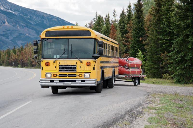 De gele bus draagt twee rode boten royalty-vrije stock afbeelding