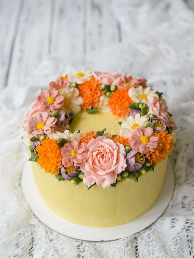 De gele die roomcake met buttercream wordt verfraaid bloeit - pioenen, rozen, chrysanten, scabiosa, anjers - op witte houten rug stock afbeelding