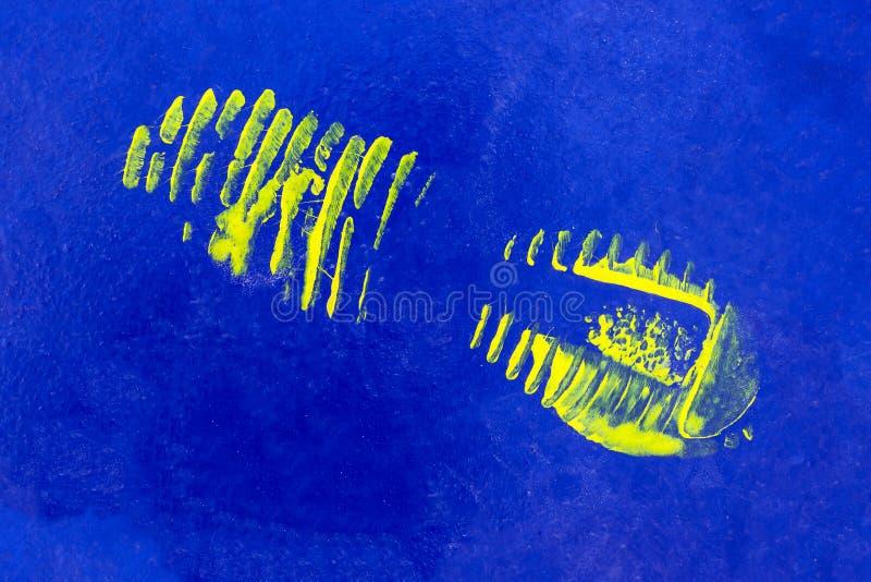 De gele druk van de verfschoen op een blauwe achtergrond Textuur Dek van stock fotografie