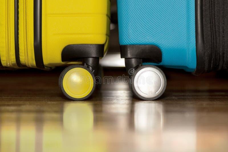 De gele en blauwe koffers op vloer, sluiten omhoog Reis en Vakantieconcept stock fotografie
