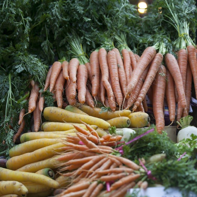 De Gele en oranje bossen van wortelen op de landbouwbedrijfmarkt stock fotografie