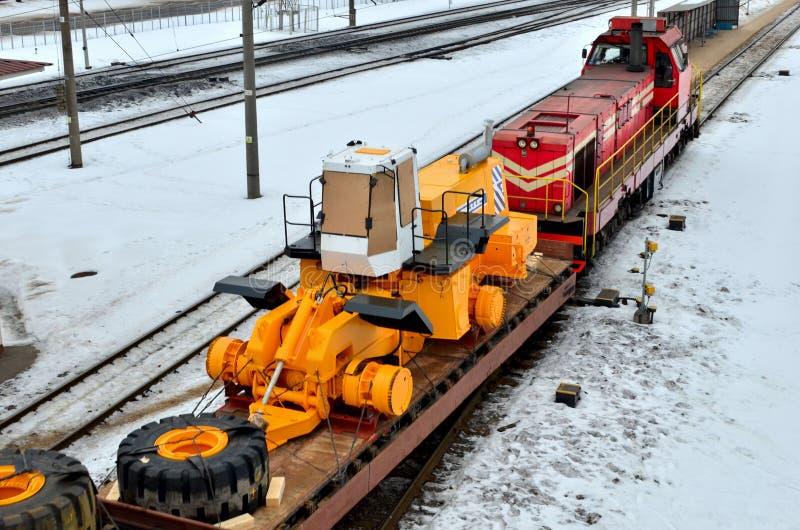 De gele en voorlader die in delen wordt gedemonteerd wordt geladen op een platform van de ladingsspoorweg stock fotografie