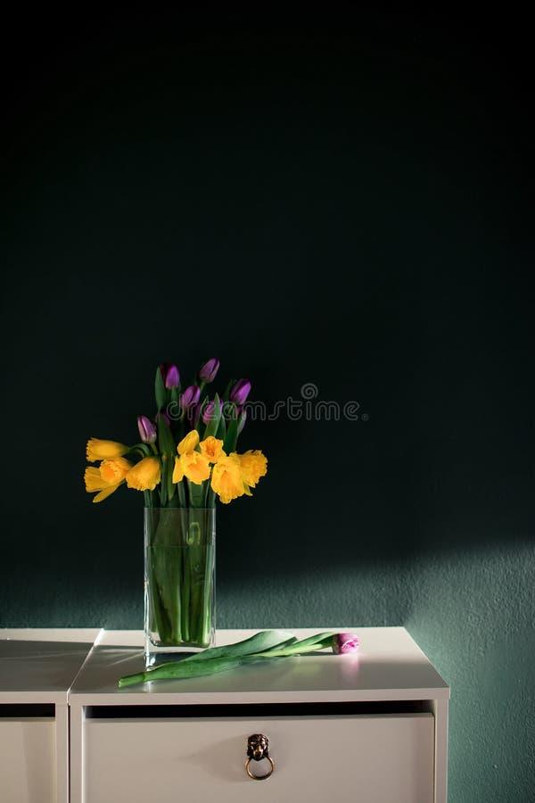 De gele gele narcis bloeit met purpere tulp die in vaas met groene muur volgende slechte mand bloeien op witte planken stock foto