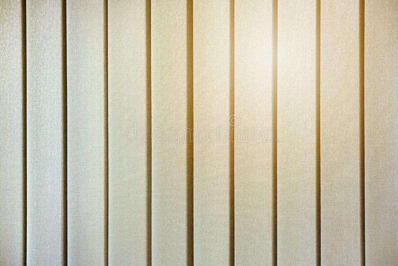 De gele gloed van de zon door de gesloten verticale zonneblinden op de vensters royalty-vrije stock fotografie
