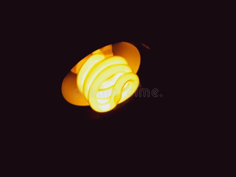 De gele gloeilampenlamp, het schrijven, bestuderen, die creatieve donkere Verandering als achtergrond uw gloeilampen lezen en ver stock foto's