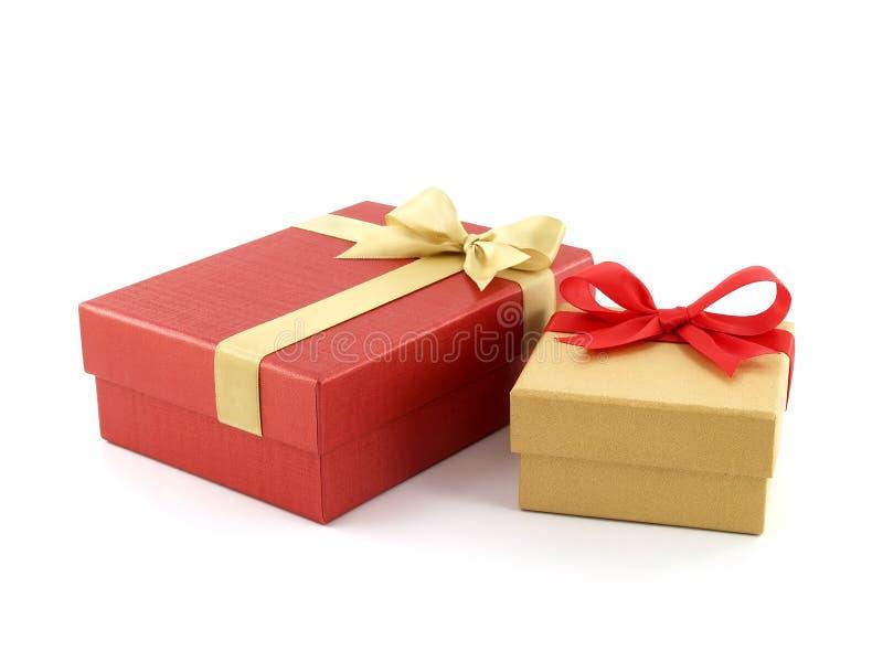 De gele gouden doos van twee giftdozen met rode lintboog en rode doos met gouden die lintboog op witte achtergrond wordt geïsolee stock foto's