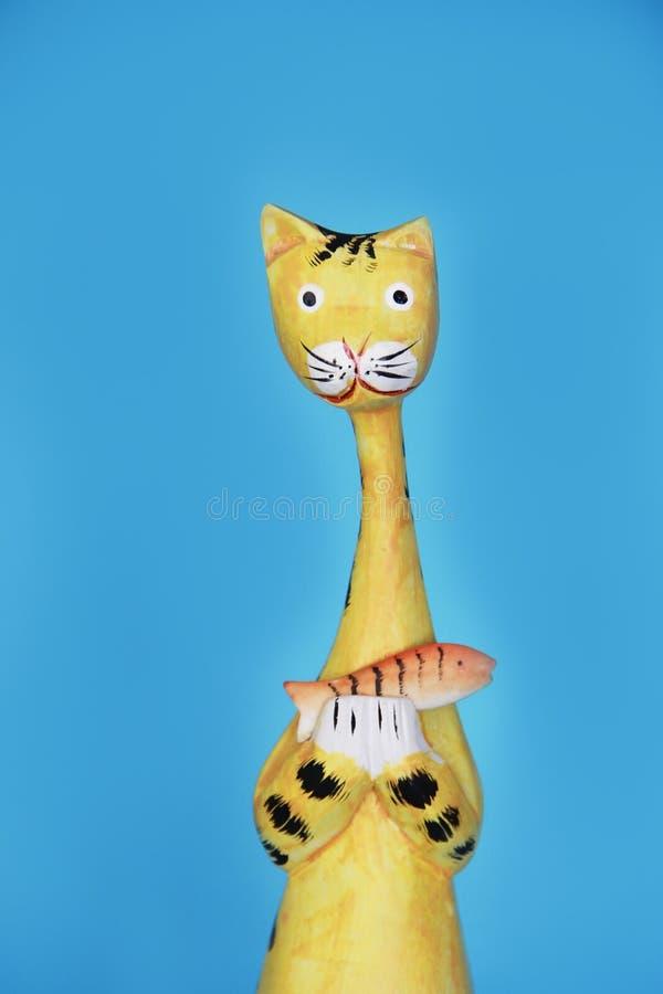 De gele houten kattenherinnering houdt een oranje vis in zijn poten stock foto