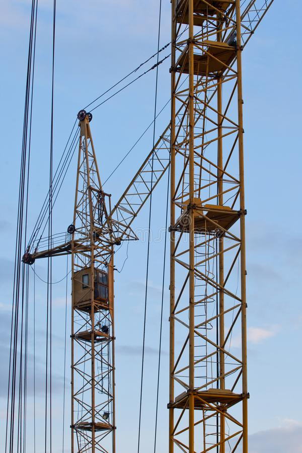 De gele kraan van de bouwtoren tegen een blauwe hemel stock fotografie