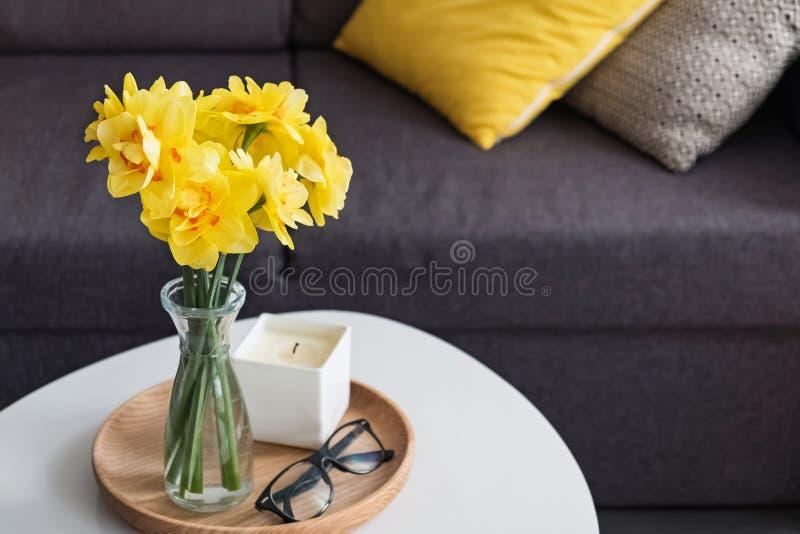 De gele lente bloeit in een vaas die zich in de woonkamer op de coffelijst bevinden stock foto's