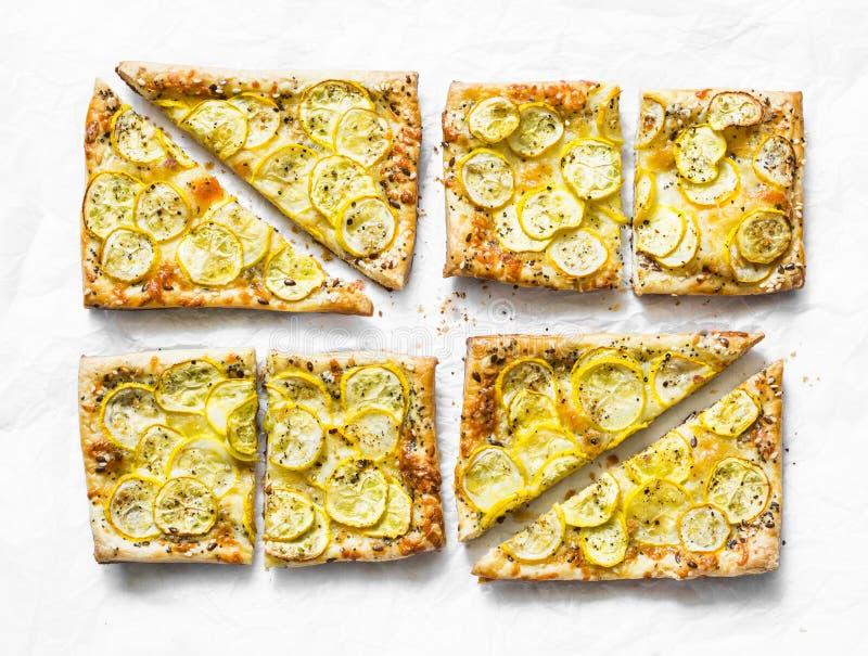 De gele minitaartjes van het courgettebladerdeeg op een lichte achtergrond, hoogste mening Smakelijke snack, tapas royalty-vrije stock afbeelding