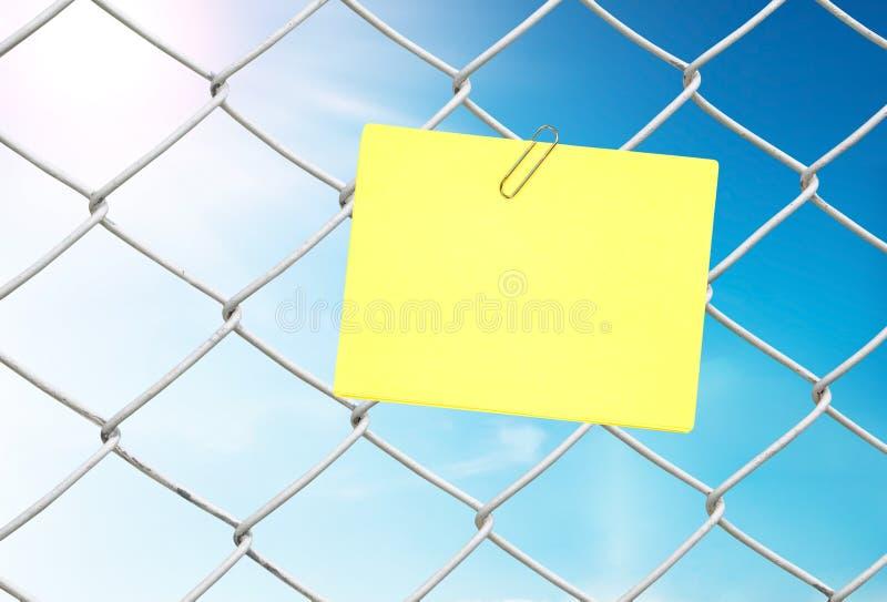 De gele nota over kettingslink omheining ziet blauwe hemel stock fotografie