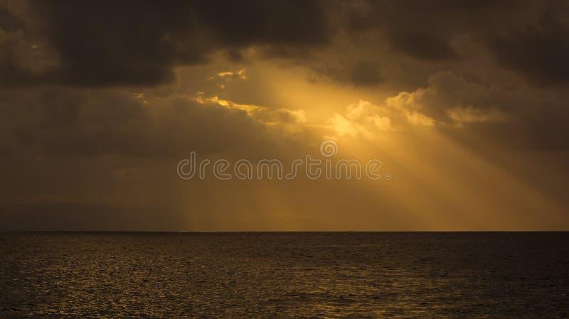 De gele, oranje zonnestralen met wolken over het overzees, hemel glanst royalty-vrije stock foto's