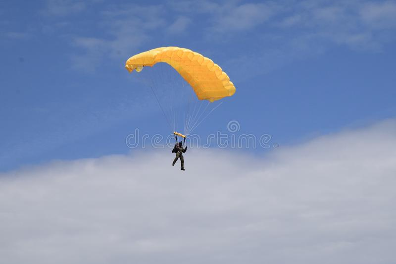 De gele parachutistmens geniet van zijn eerste vlucht stock afbeelding