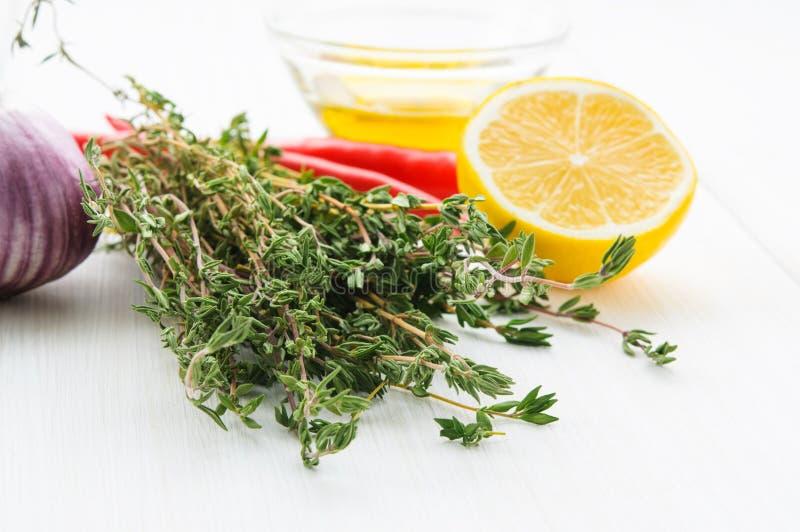 De gele peper van de de takspaanse peper van citroen halve, groene thyne, olijfolie, knoflookhoofd op witte houten lijst of geïso stock afbeelding