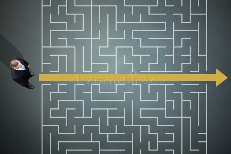 De Gele Pijl die van Businesspersonstanding next to door Labyrint gaan stock foto's