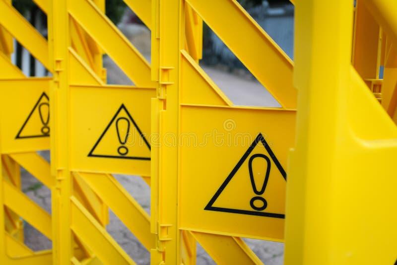 De gele plastic omheining met uitroeptekens, concept verbod, besteedt aandacht stock afbeeldingen