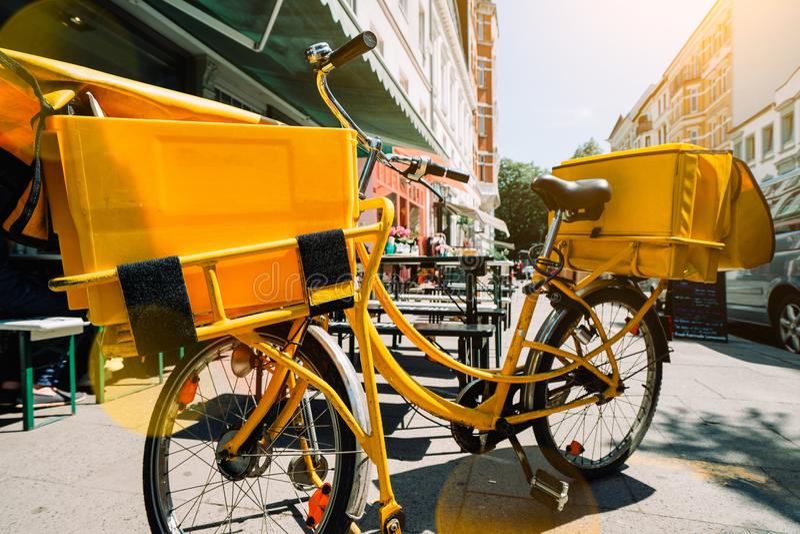 De gele postfiets maakte einde dichtbij de bouw voor levering Hamburg, Duitsland stock foto