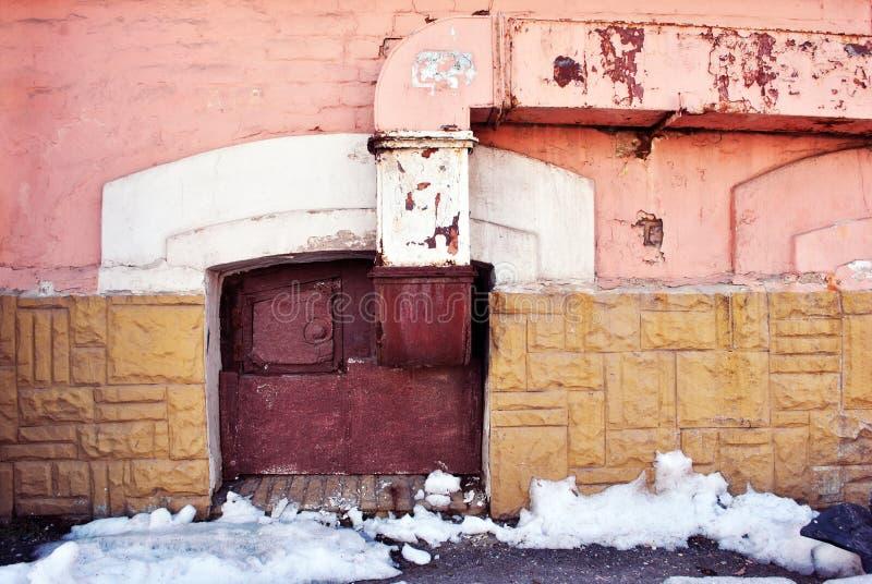 De gele, roze kleurenmuur met oud rood scheepte op venster op het grondniveau in, ventilatiepijp, die sneeuw op asfalt smelten stock afbeeldingen