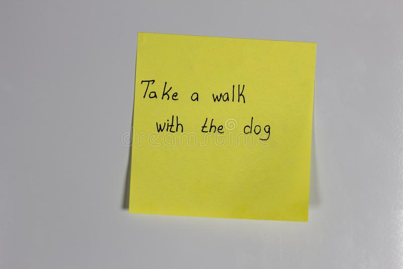 De gele sticker op de ijskast met een inschrijving neemt een gang met de hond royalty-vrije stock afbeeldingen