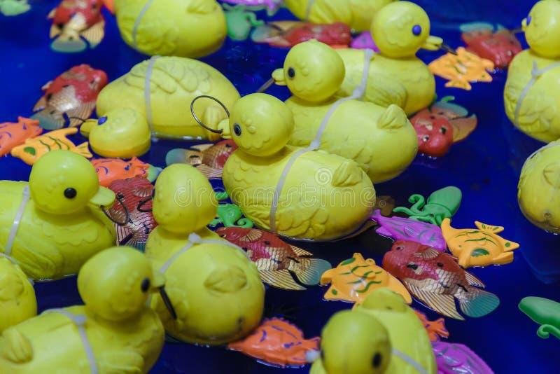 De gele stuk speelgoed rubbervlotters van de eendfamilie in het water stock foto