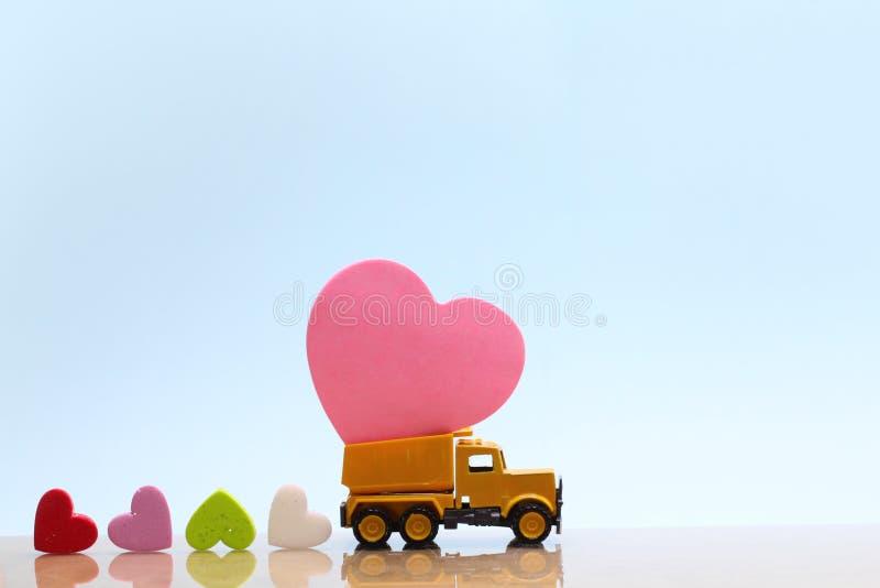 De gele stuk speelgoed vrachtwagen draagt roze hart en vele kleurrijke harten op blauwe achtergrond stock afbeeldingen