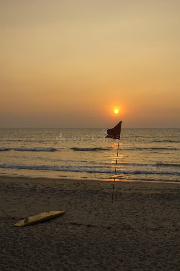 De gele surfplank ligt op het zand dichtbij de rode vlag tegen de oceaan tijdens zonsondergang royalty-vrije stock foto
