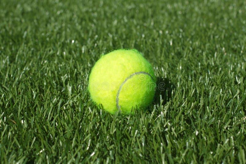 De gele tennisbal legt op de synthetische close-up van het grashof royalty-vrije stock fotografie