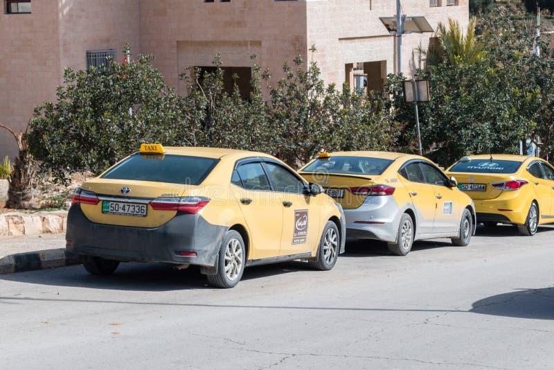 De gele tribune van taxiauto's die aan een straatkant in Wadi Musa naast ingang aan Petra wordt geparkeerd stock afbeeldingen