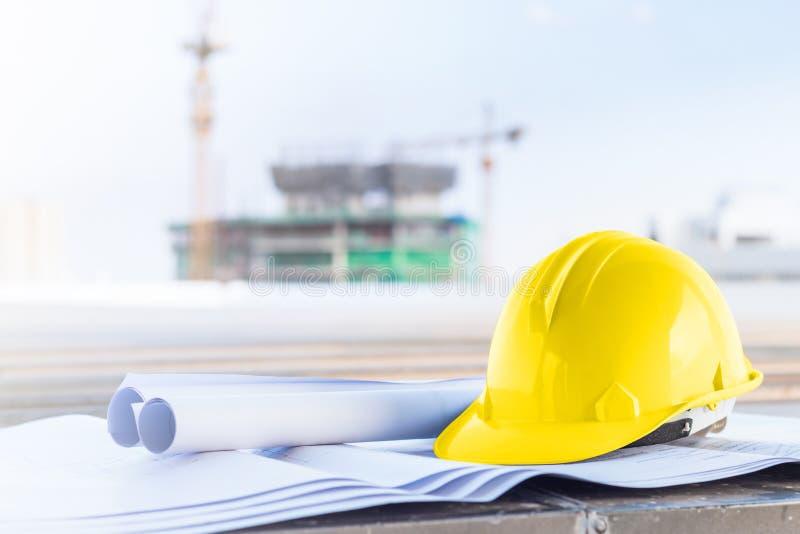 De gele veiligheidshelm en de blauwdruk bij bouwwerf royalty-vrije stock afbeeldingen