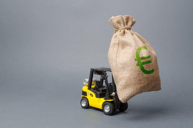 De gele vorkheftruck draagt een grote zak geld Het aantrekken van investering in ontwikkeling, modernisering van productie en zak royalty-vrije stock foto's