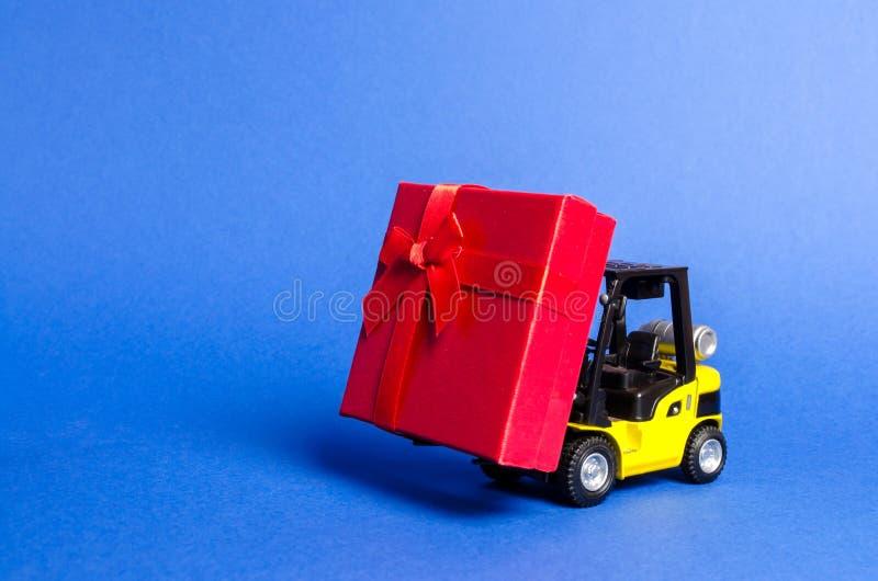De gele vorkheftruck draagt een rode giftdoos met een boog Aankoop en levering van een heden kleinhandels, kortingen en wedstrijd royalty-vrije stock afbeelding