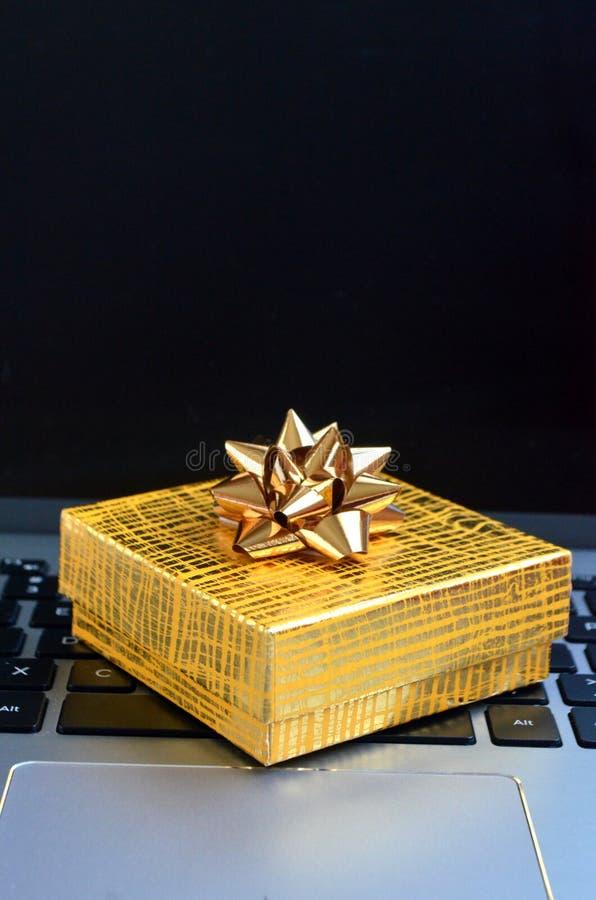 De gele zitting van de giftdoos op laptop dichte omhooggaand van het computertoetsenbord royalty-vrije stock foto's