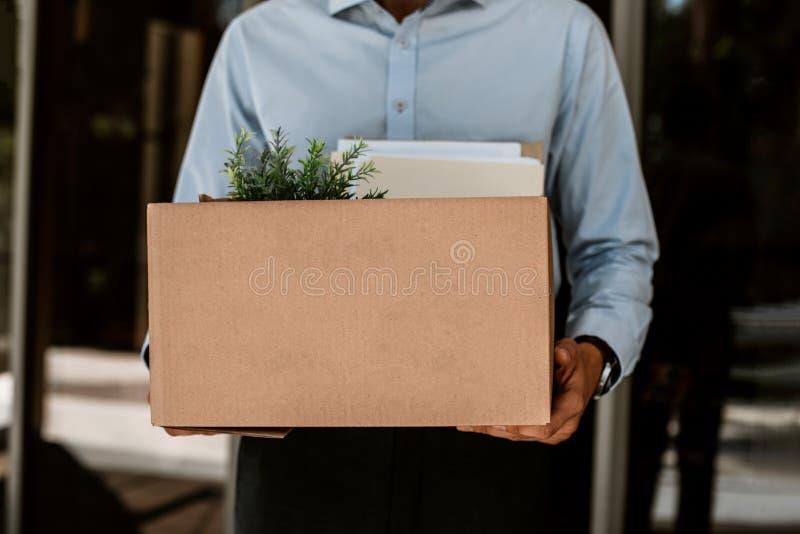 De geloste kerel houdt karton met bezittingen stock fotografie