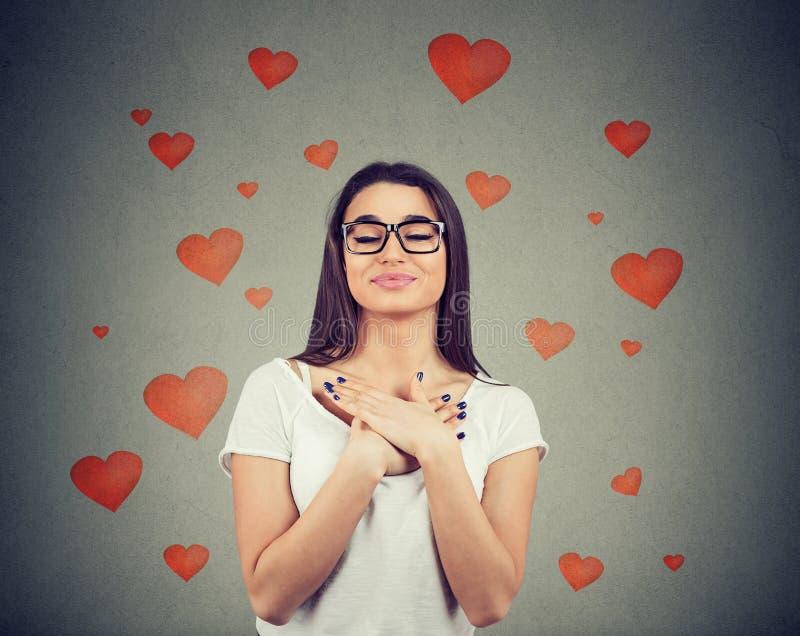 De gelovige vrouw met gesloten ogen houdt handen op borst dichtbij hart royalty-vrije stock foto's