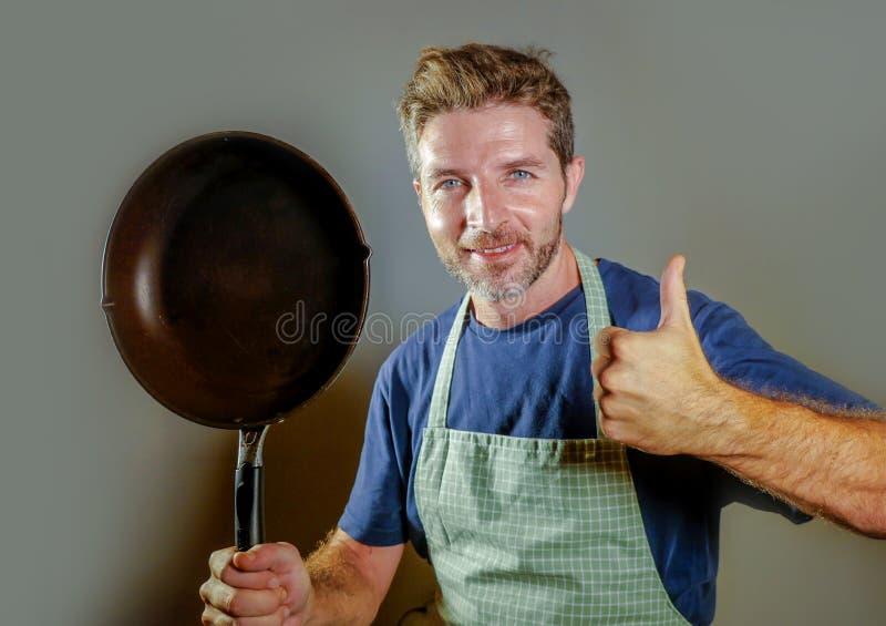 De gelukkige aantrekkelijke mens van de huiskok met het koken van pan die tevreden en trotse gevende duim glimlachen omhoog binne stock afbeelding