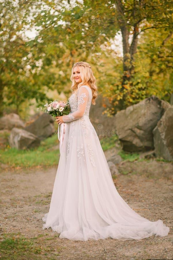 De gelukkige aantrekkelijke mooie bruid met leuke wangen en een zacht kapsel van blond haar is gekleed in grijze luxueus stock foto's