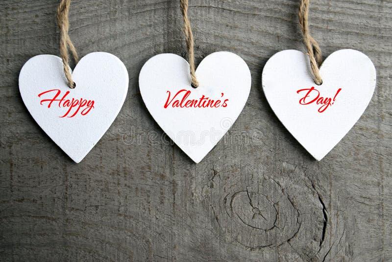 De gelukkige Achtergrond van de Dag van Valentijnskaarten Decoratieve witte houten harten op grijze rustieke houten achtergrond m stock afbeelding