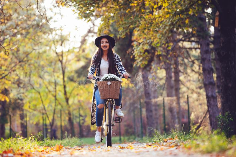 De gelukkige actieve fiets van de vrouwen berijdende fiets in het park van de dalingsherfst royalty-vrije stock foto