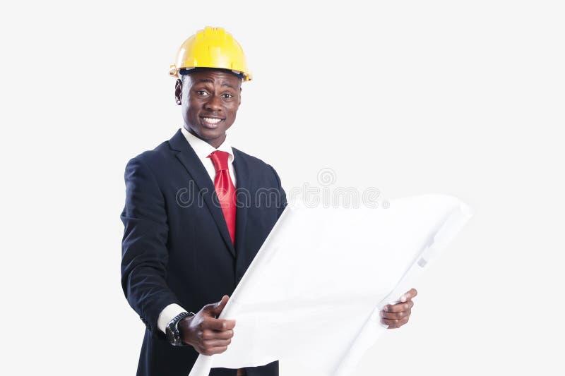 De gelukkige Afrikaanse Amerikaanse blauwdruk van de bouwvakkerholding royalty-vrije stock fotografie