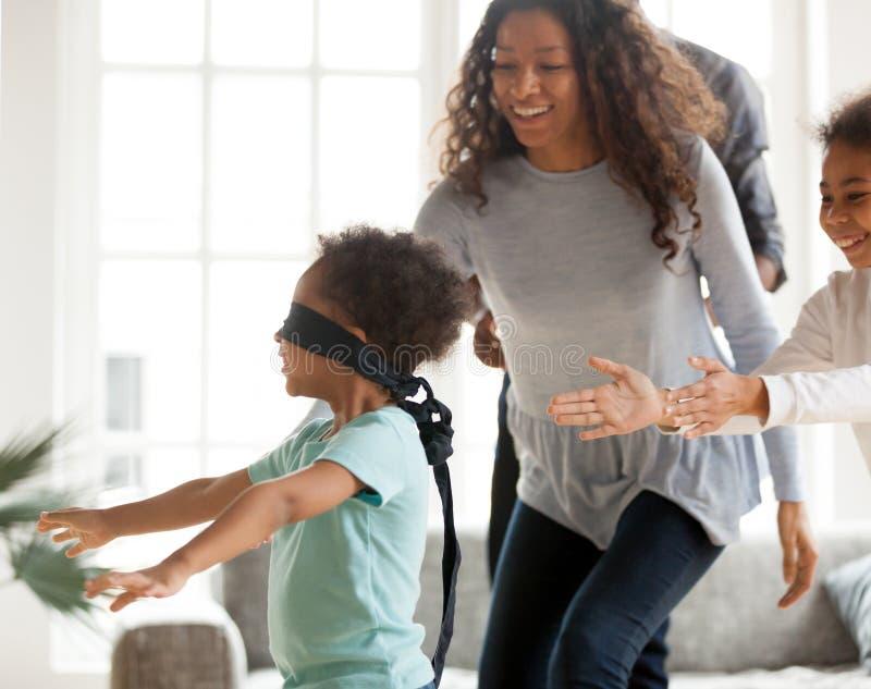 De gelukkige Afrikaanse Amerikaanse familie het spelen huid - en - zoekt thuis royalty-vrije stock fotografie