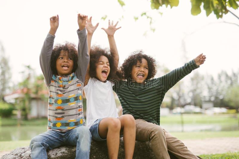 De gelukkige Afrikaanse Amerikaanse vreugdevol vrolijk en kinderen die van weinig jongensjonge geitjes lachen Concept geluk stock foto's